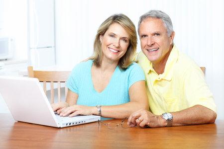 senior ordinateur: Couple senior travaillant avec portable � la maison