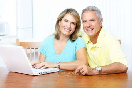 family sofa: Senior couple  working with laptop at home