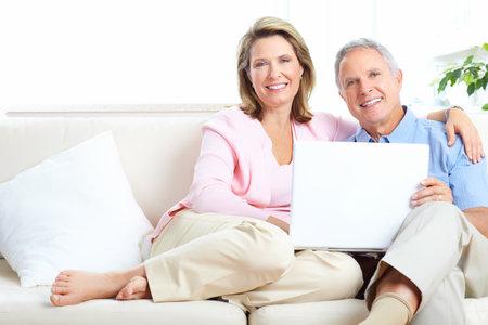 prendre sa retraite: Couple senior travaillant avec portable � la maison