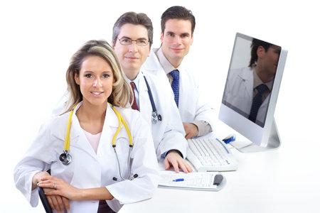 uniforme medico: Doctores en medicina sonrientes trabajar con un ordenador. Aislados sobre fondo blanco