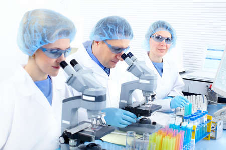 Science team working with microscopes at  laboratory Stock Photo - 8554931