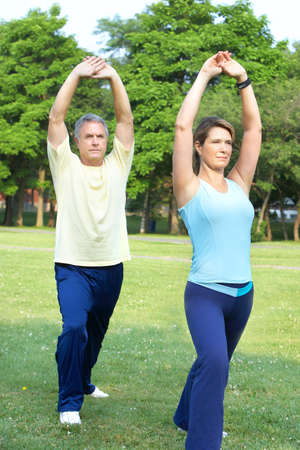 woman working out: Happy elderly seniors couple working out in park