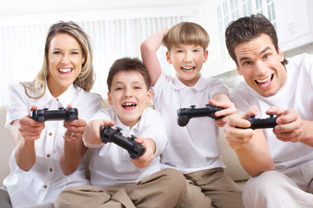 Happy family. Father, mother and children playing a video game   Imagens