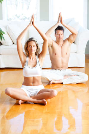 home health care: Young man and woman woman doing yoga in the sunny room