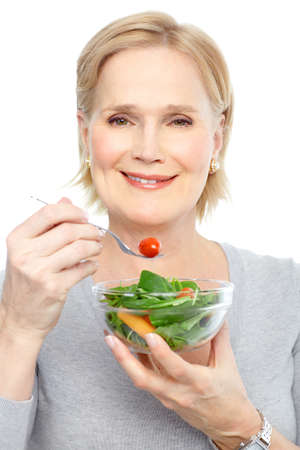 eating: Mature smiling woman  eating salad,  fruits and vegetables.   Stock Photo