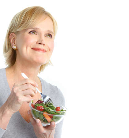 Mature smiling woman  eating salad,  fruits and vegetables.   photo