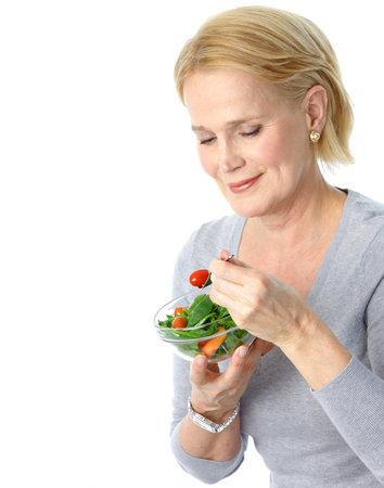euforia: Mujer madura sonriente comer ensaladas, frutas y verduras.   Foto de archivo