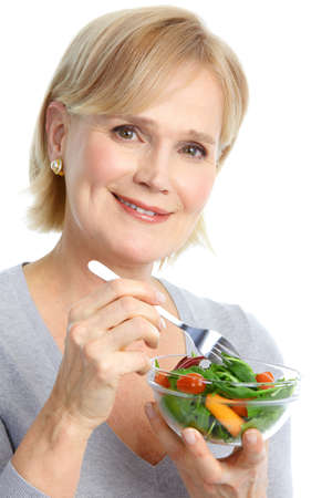 woman eat: Mature smiling woman  eating salad,  fruits and vegetables.   Stock Photo