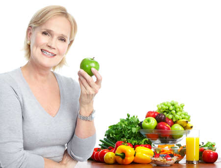 Mature smiling woman  with apple,  fruits and vegetables.  photo