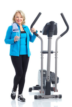 elliptical: Gym & Fitness. Smiling elderly woman working out. Isolated over white background