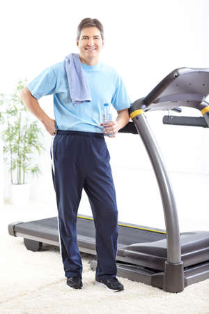 Fitness man with a bottle of spring water near the treadmill photo
