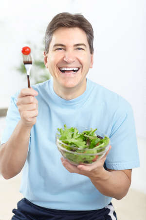 Mature smiling man  eating salad,  fruits and vegetables.  photo