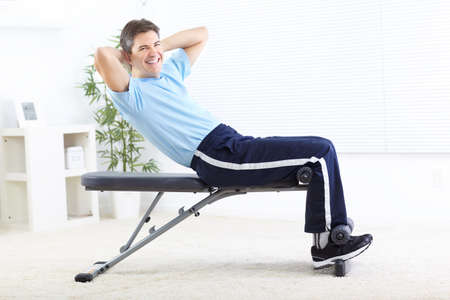 Smiling strong man working out at home photo