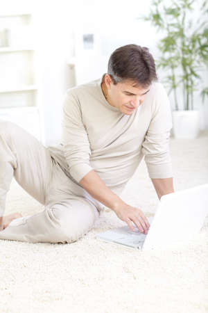 floor covering: Young smiling man working with laptop on the carpet at home