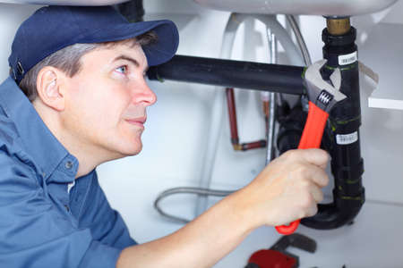 pipe wrench: Mature plumber fixing a sink at kitchen  Stock Photo
