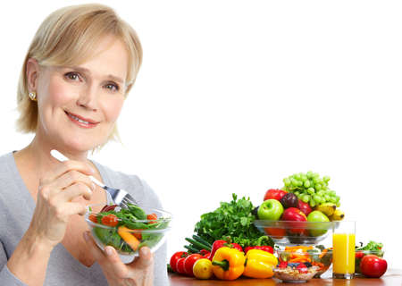 fruit salads: Mature smiling woman  eating salad,  fruits and vegetables.   Stock Photo
