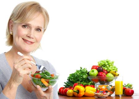 ensalada de frutas: Mujer madura sonriente comer ensaladas, frutas y verduras.   Foto de archivo