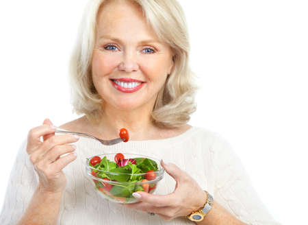 Mature smiling woman  eating salad,  fruits and vegetables. Stock Photo - 8735936