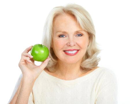 Volwassen lachende vrouw met een groene appel