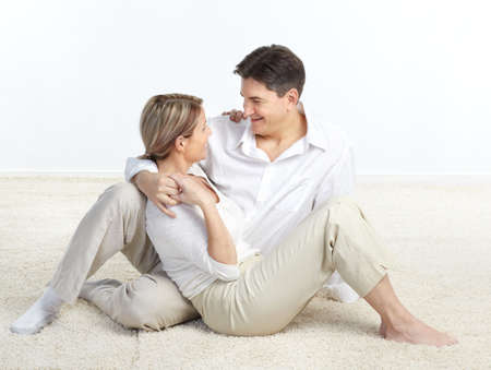 Happy smiling couple in love sitting on the carpet  版權商用圖片