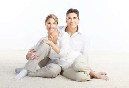 Happy smiling couple in love sitting on the carpet