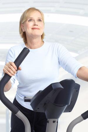 Gimnasio & Fitness. Sonriente anciana trabajando.  Foto de archivo