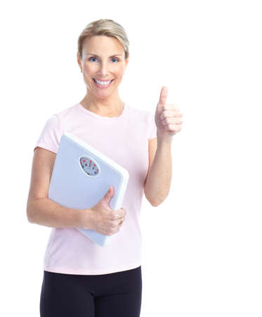 svelte: Gym & Fitness. Smiling mature woman with a bathroom scale  Stock Photo