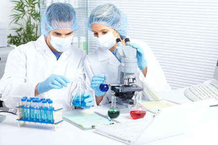 laboratorian: Science team working with microscopes at  laboratory  Stock Photo