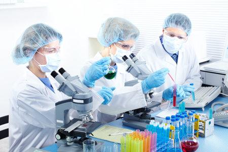 bata de laboratorio: Equipo de ciencia trabajando con microscopios de laboratorio  Foto de archivo