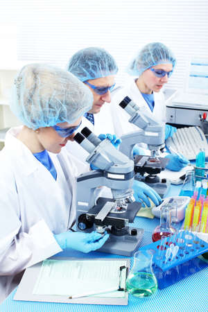 investigador cientifico: Equipo de ciencia trabajando con microscopios de laboratorio  Foto de archivo