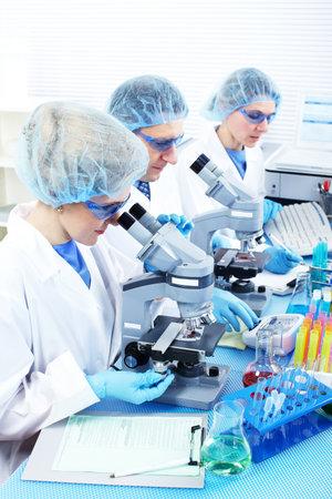 Science team werken met microscopen bij laboratorium  Stockfoto