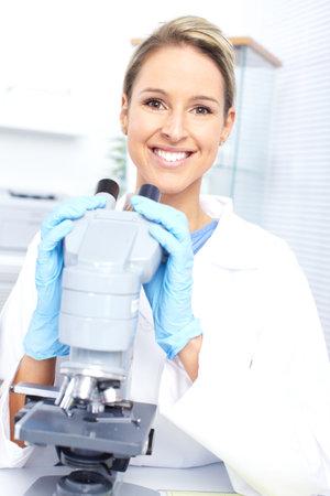 Vrouw die werkt met een microscoop in lab Stockfoto