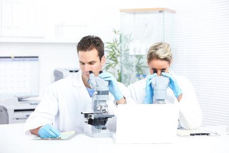 bata de laboratorio: Equipo de ciencia trabajando con microscopios en un laboratorio Foto de archivo