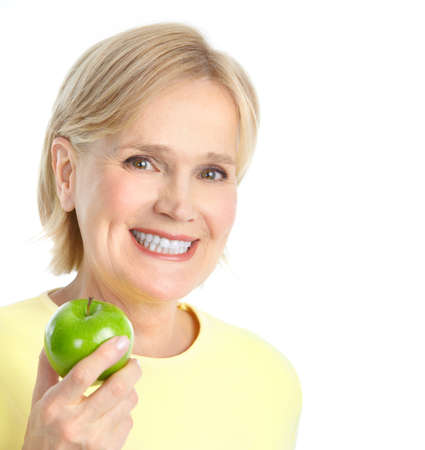 senior eating: Mature smiling woman with a green apple