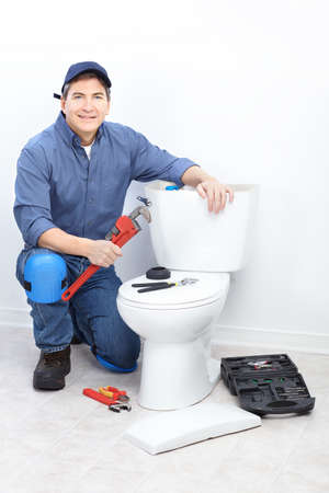 Mature plumber near a flush toilet   photo