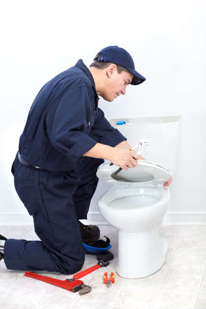 Mature plumber near a flush toilet 