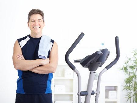 eliptica: Gimnasio Fitness &. Hombre sonriente trabajando.