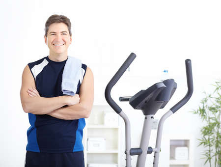 home trainer: Gym & Fitness. Smiling man working out.
