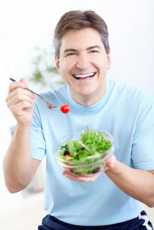 Oudere lachende man eten salade, fruit en groenten.