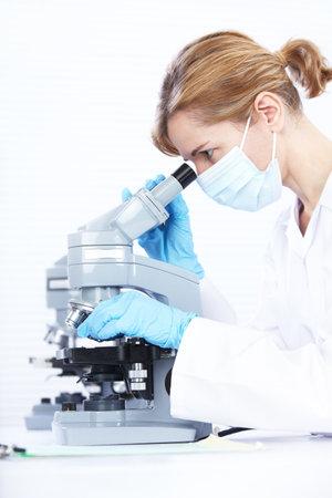 scienziati: Donna che lavora con un microscopio in laboratorio  Archivio Fotografico