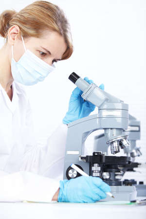 laboratory technician: Woman working with a microscope in lab