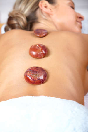 Beautiful young woman with stones on the back getting a spa massage  photo