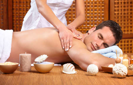 massaging: young handsome man getting a massage
