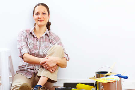 smiling beautiful woman painting interior wall of home.  Stock Photo - 8863724