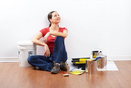Lachende mooie vrouw schilderij interieur wand van huis.  Stockfoto - 8863726