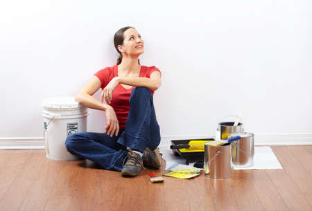 paints: smiling beautiful woman painting interior wall of home.   Stock Photo