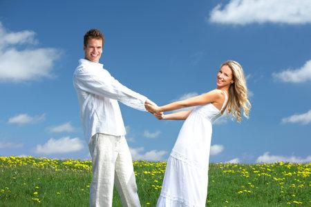 parejas jovenes: Young love par sonriendo bajo cielo azul