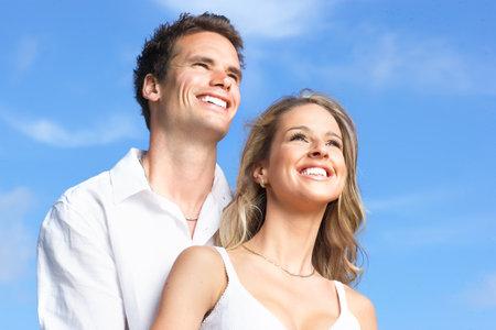 Young love couple smiling under blue sky  Фото со стока