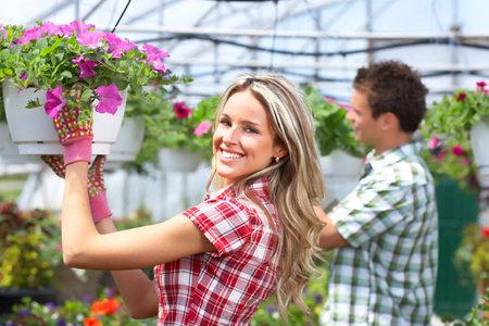 kassen: Tuinieren. Glimlachend jongeren bloemisten werken in de tuin.