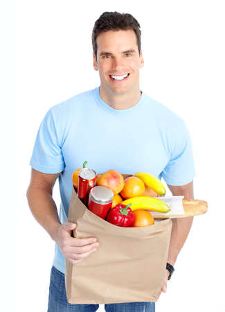 grocery shopping: smiling young man holding a shopping bag with food
